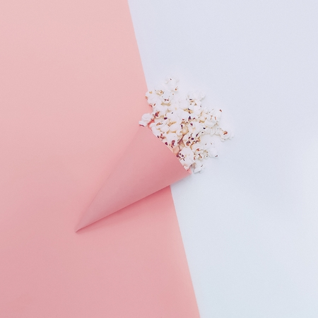 color background: Popcorn in paper envelope. Minimalism design