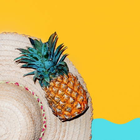 Beach time. Tropical style accessories. Hat and fresh pineapple.