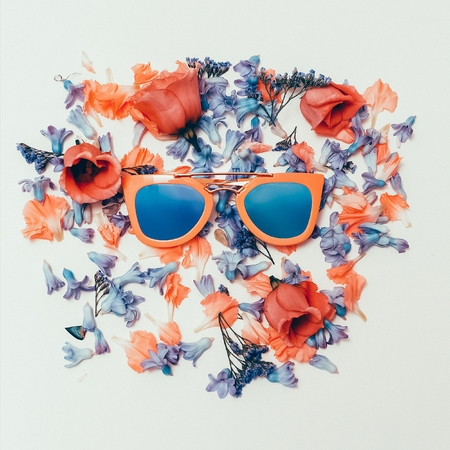 Trend Sunglasses on flowers background. Summer is coming. Stock Photo