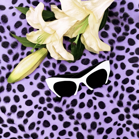 White sunglasses and Lily on leopard print background. Stylish summer accessory