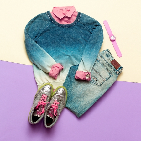 Fashion woman accessories set. Vanilla Lady. jeans, Sweater and shirt hipster trendy girl. creative look. Vanilla and blue pastel background, fashion sneakers and watches