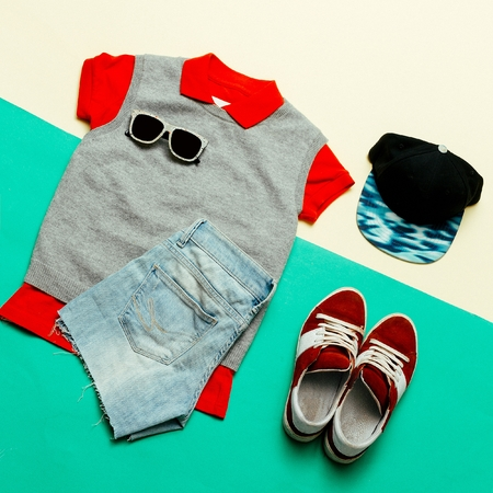 strip shirt: Stylish clothes. Skateboard fashion. Focus on red. Caps, Sneakers, shorts. Active style Stock Photo
