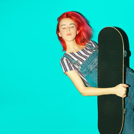 Pretty teenager girl with pink hair and skateboard