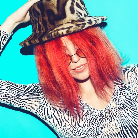 red animal: Model in fashion clothes animal print. Hat Fashion Accessory. Stylish red hair
