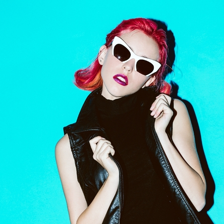 Model Glam Rock style. Red hair trend and stylish sunglasses Leather Jacket