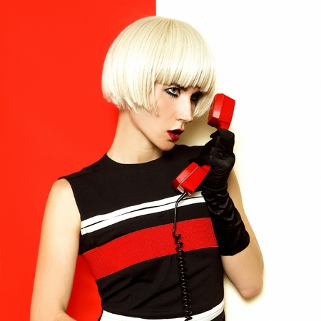 Blond retro style with vintage phone and vintage clothing. Minimal Fashion. Bob kare