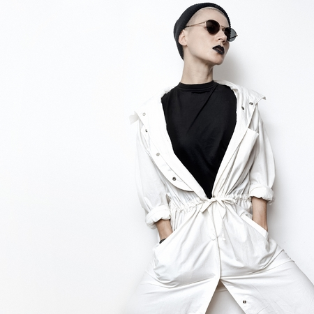 trend: hipster model. Swag. Minimal style. Beanie cap and stylish sunglasses. Vintage Glamour. Trendy white coat. Outfit Black fashion stylish makeup lips Be in trend Stock Photo