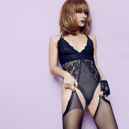 Sexy model in lacy black underwear and stockings. Lace gloves. Black lipstick. Graceful passion fashion concept details trend lingerie