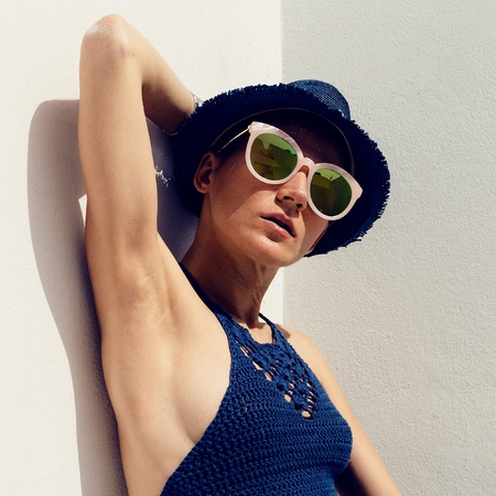 girl in a hat: hipster sunny outdoors Stylish Girl Boho trend sunglasses, knitted top and straw hat. Relax Summer Fashion