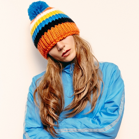 pompon: Stylish brunette in a hat with pompon and a blue jacket Snowboard fashion Stock Photo