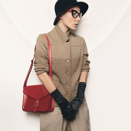 Vintage Fashion Model Beige classic costume and stylish Accessories. Black gloves. Glasses, hat. Red Bag. Fashion concept. Glamor and retro time