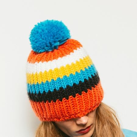 pompon: Stylish brunette in a knitted hat with pompon Snowboard fashion