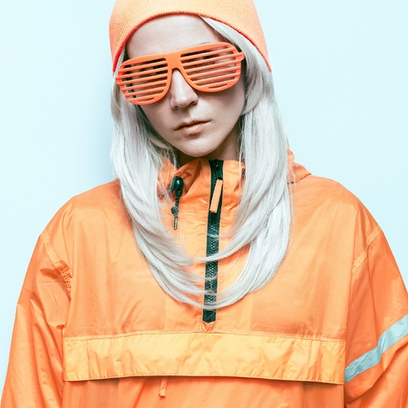 dubstep: blond model in a fluorescent orange clothes Fashion Party Swag