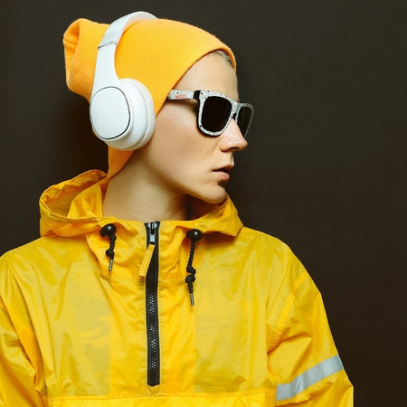 dubstep: Model DJ in stylish yellow sportswear and accessories. Bright season. Snowboard fashion style party Stock Photo