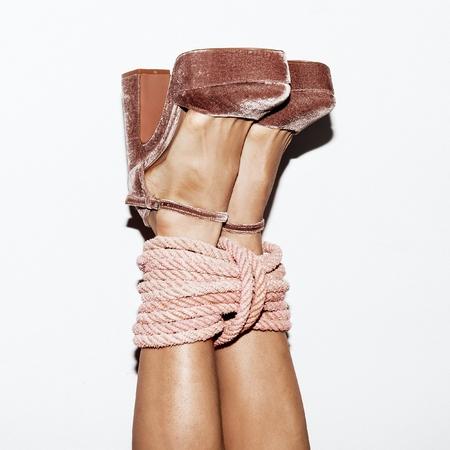 Les pieds des filles sur le mur attaché avec une corde. Espiègle