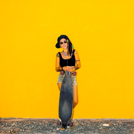 Cool Teenager girl on background  yellow wall with a skateboard