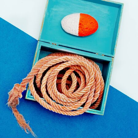 Ocean souvenirs. Sea rope and stone in the box. Minimal design art