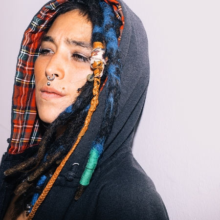 Portrait of Latin girl with dreadlocks and piercing. Street fashion style
