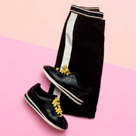 Fashion Outfit for women. Black stylish clothes. Sports Urban. Minimal. Top view Sneakers and trousers Stockfoto