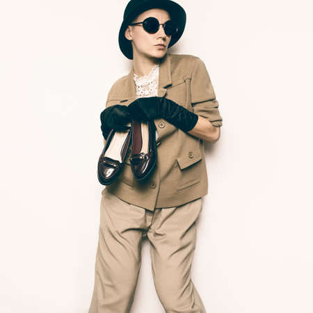 Funny Vintage Fashion Model. Beige classic costume and stylish Accessories. Black Gloves. Glasses, Hat. Fashion concept. Glamor and retro. Trend Vintage Shoes