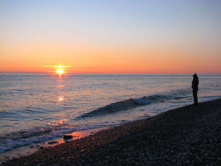 lonely girl on winter sunset beach. black sea photo