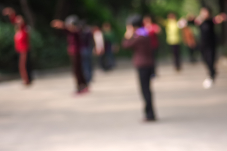 chi kung: Blurred image of   chinese people practicing  tai chi in Park Stock Photo