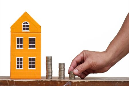 home finances: Male hand is stacking coins for  Home Finances Stock Photo
