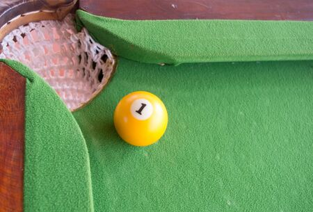 snooker tables: yellow ball near hole on pool game Stock Photo