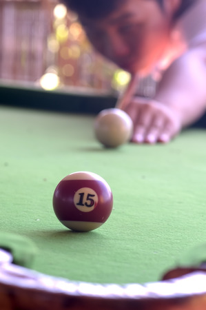 cue sticks: a man aim the last ball in pull game.