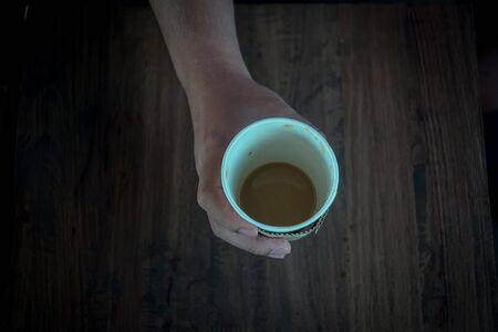 vignetted: Hand hold a cup of coffee on wooden desk.Photo in vintage style with  vignetted