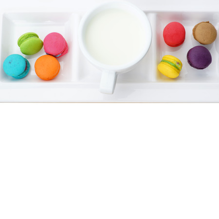 Colorful macarons and milk cup isolated on white Foto de archivo