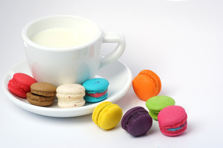 Colorful macarons and milk cup on white Foto de archivo