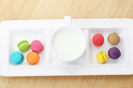 Colorful macarons and milk cup on wooden background