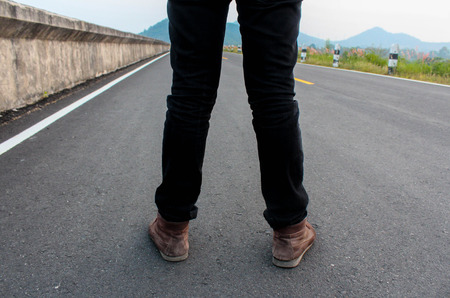 obscenity: Low portrait of a mans legs and shoes from back on the road Stock Photo