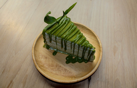 antecedents: Green tea crepe cake with green sauce on wood plate background