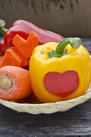 bell peper: Sweet pepper and carrot in bamboo basket over wood background Stock Photo