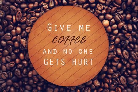 Quote about coffee on wood background over coffee beans. Coffee beans background. photo