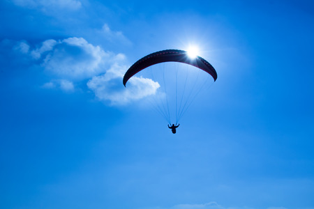 paraglider: Paraglider on the blue sky in the sun and clouds. Stock Photo