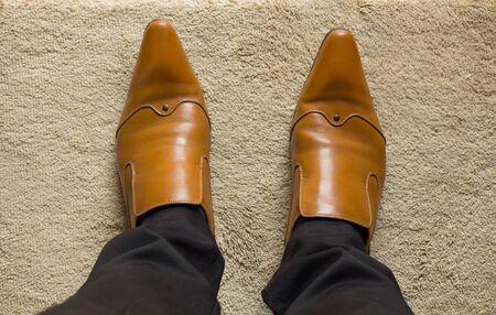 piernas hombre: Piernas Hombre en zapatos marrones en la estera. Foto de archivo