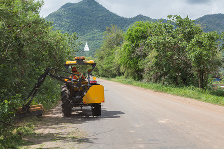mowing grass: mowing grass shoulder along road in public space with big orange tractor mower