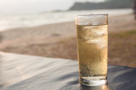 Glass of whiskey on a blurred background of the sea.