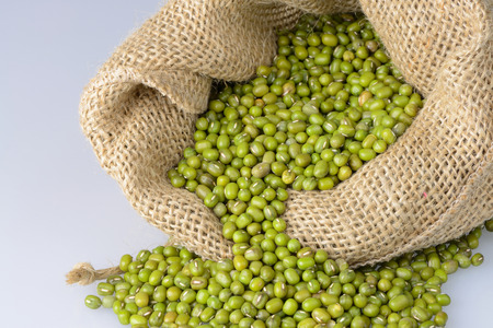 munggo: Mung bean seeds spilling from a sack. Stock Photo
