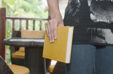 young woman, serious student (female) hand holding book and reading on background of a home