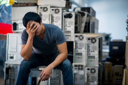Sad asian technician man with old computer