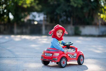 Asian child boy in a red hat in a red toy car in the street Stockfoto