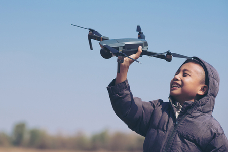 Cute boy holding drone at meadow, Child playing with drone outdoors at summer day