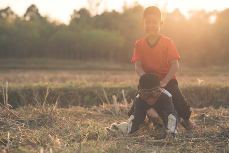 children having fun and playing with sunset. two cheerful boys sit on the field
