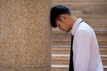 Geschäftsmann weint, verlassen in Depressionen verloren, sitzt auf der Betontreppe der Bodenstraße und leidet unter emotionalen Schmerzen