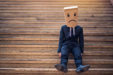 business man sitting and paper bag with a painted face on it instead of a face sad, the concept of duplicity in business Foto de archivo