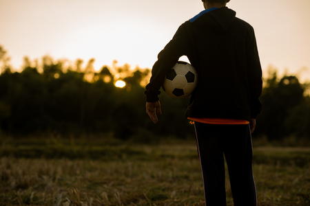 Boy playing soccer in the sunset